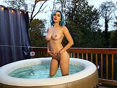 Dyed hair busty girl masturbates in a hot tub